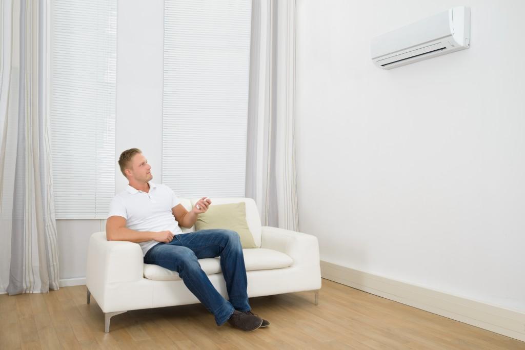 Man Adjusting The Temperature Of Air Conditioner