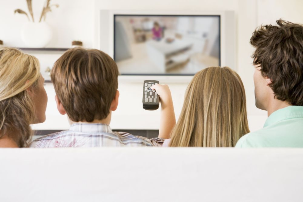 Families sat on sofa at home watching tv